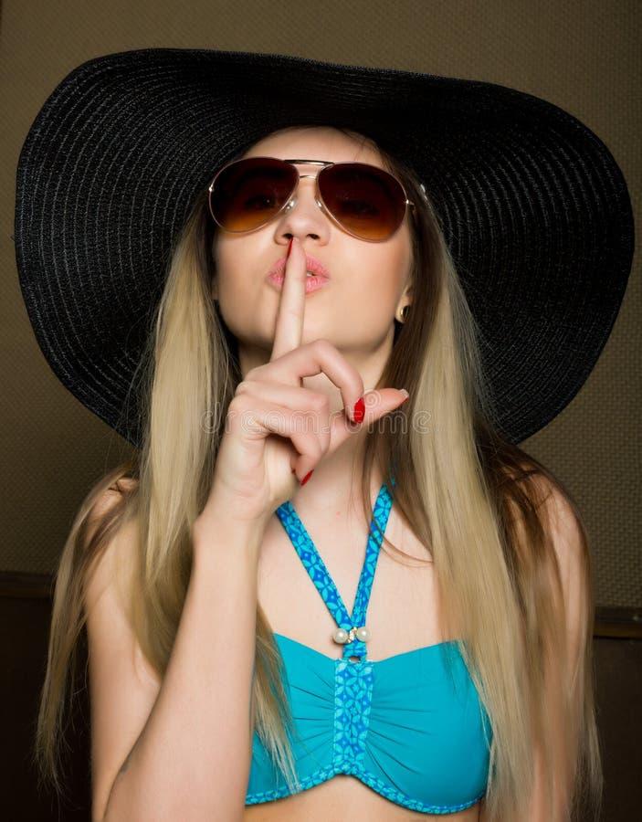 Närbild av den attraktiva brunettkvinnan i en bikini, en stor hatt och en solglasögon som sätter ett finger på hennes kanter royaltyfri foto