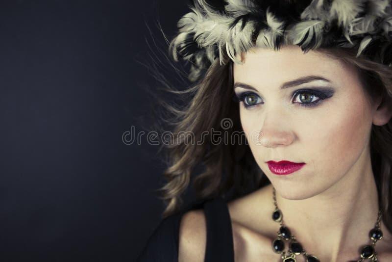 Närbild av den bärande fjäderhatten för ung kvinna royaltyfri foto