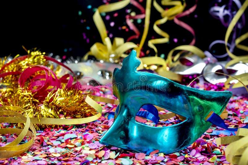 Närbild av den blåa karnevalmaskeringen över konfettier och mång--färgade banderoller royaltyfri foto