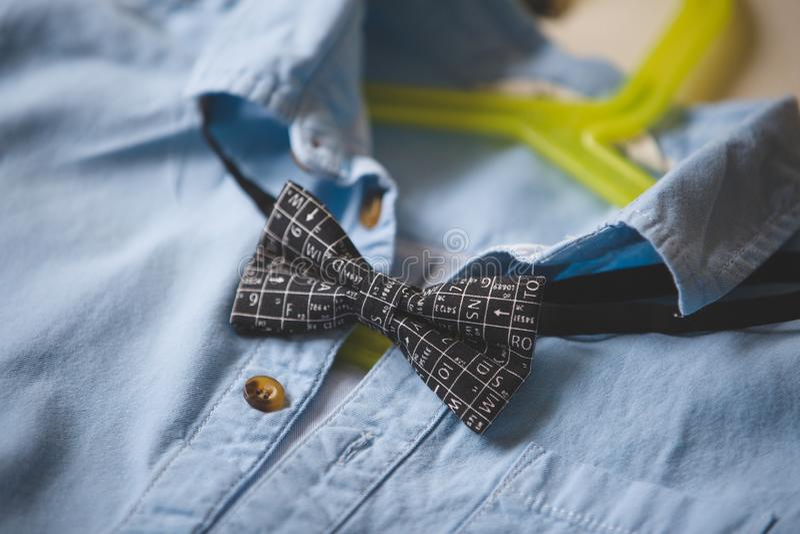Närbild av den blåa skjortan med en fluga på en hängare Svart fluga med vetenskapliga symboler kl?der Dräkt för specialt tillfäll royaltyfria foton