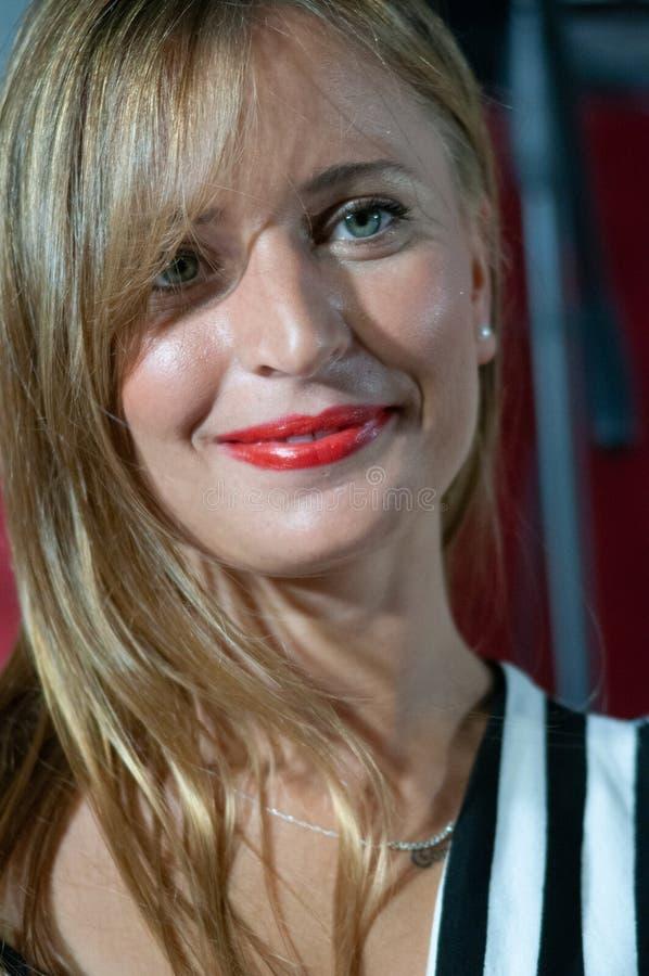 Närbild av den blonda le flickan med gröna ögon Perfekt framsidamakeup med röda kanter royaltyfri fotografi