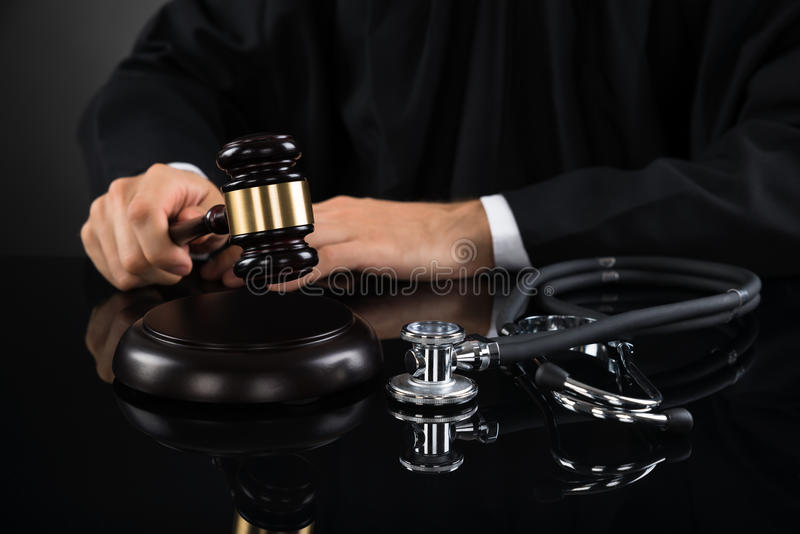 Närbild av den domareHitting Gavel With stetoskopet royaltyfri foto