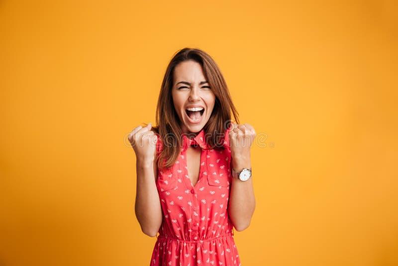 Närbild av den emotionella brunettkvinnan som håller händer i nävar, scr fotografering för bildbyråer