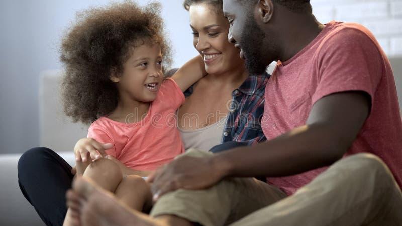 Närbild av den gladlynta familjen som tillsammans tycker om tid och har gyckel hemma arkivfoto