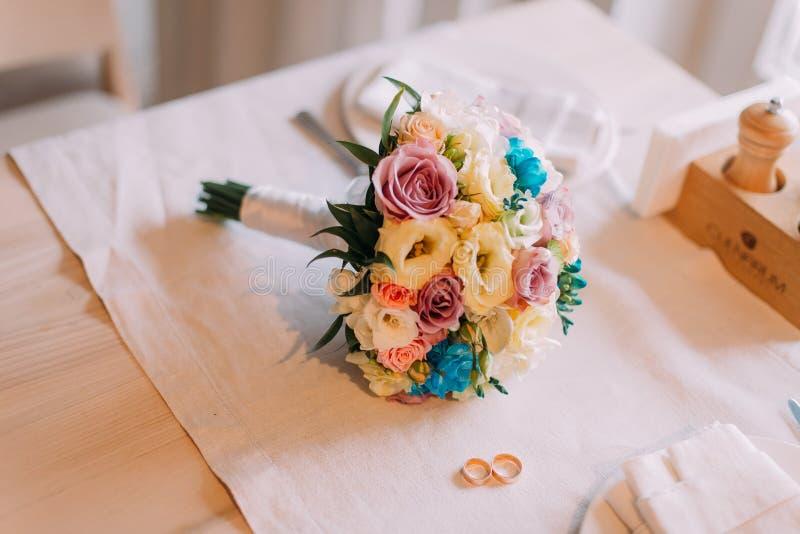 Närbild av den härliga brud- buketten med två guldbröllopcirklar royaltyfria foton