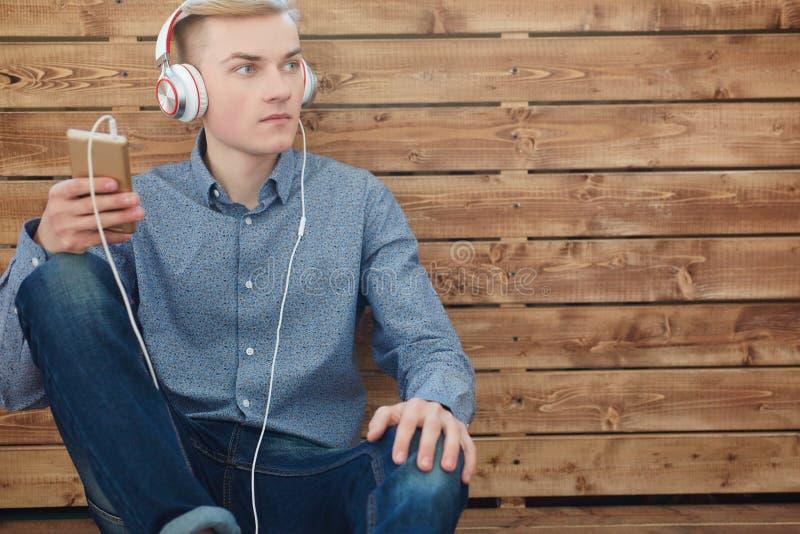 Närbild av den hållande mobiltelefonen för ung scandinavian man och lyssnande musik med leende, medan sitta på trägolvet royaltyfri bild