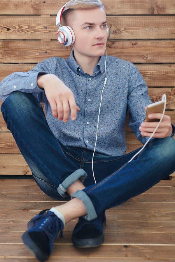 Närbild av den hållande mobiltelefonen för ung scandinavian man och lyssnande musik med leende, medan sitta på trägolvet arkivbilder