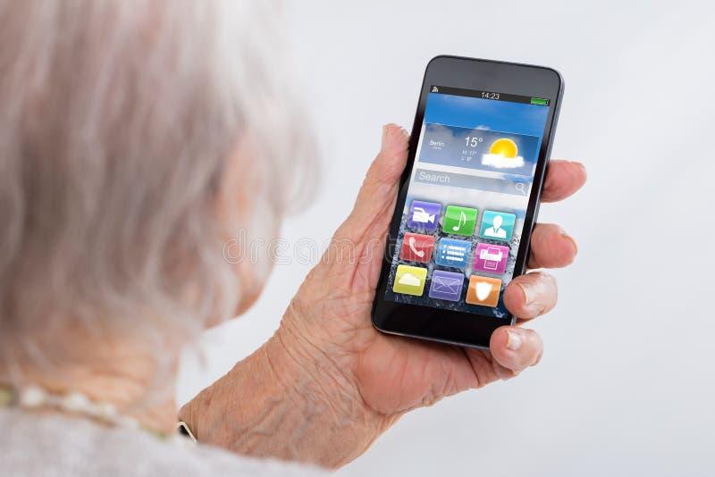 Närbild av den höga kvinnan som använder Smartphone fotografering för bildbyråer