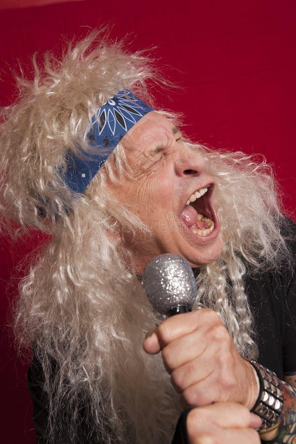 Närbild av den höga manliga sångaren som sjunger över röd kulör bakgrund arkivbild
