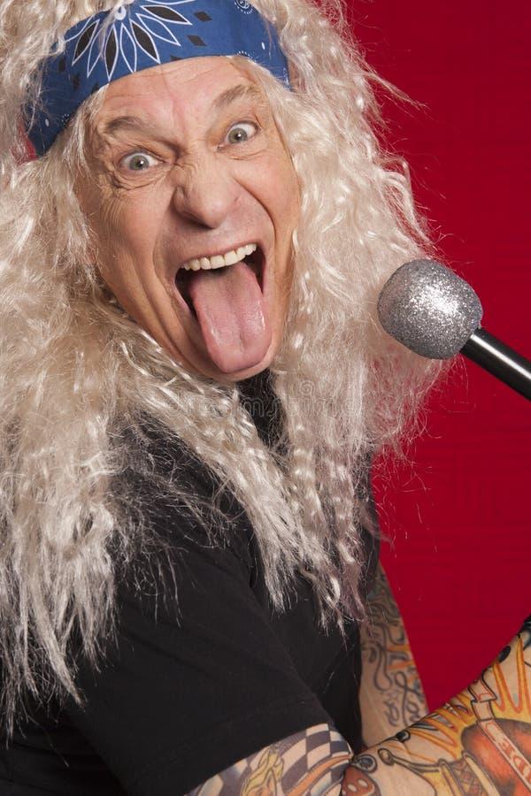 Närbild av den höga musikern som gör roliga framsidor, medan sjunga över röd bakgrund royaltyfri fotografi