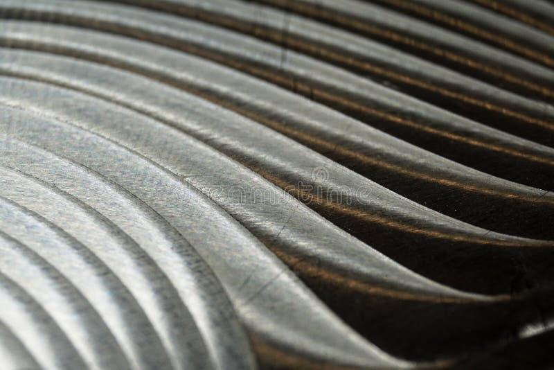 Närbild av den industriella realistiska gråa plana delen för färgrostfritt stål i partisk fokus efter industriell CNC som sänder  arkivbilder