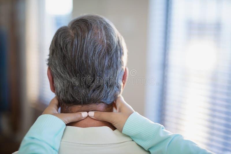 Närbild av den kvinnliga terapeuten som masserar halsen till den manliga patienten arkivfoton