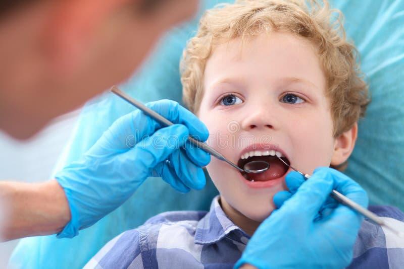 Närbild av den lilla Caucasian lockiga pojken som öppnar hans munsned boll under kontroll av det muntliga hålet av tandläkaren royaltyfria bilder