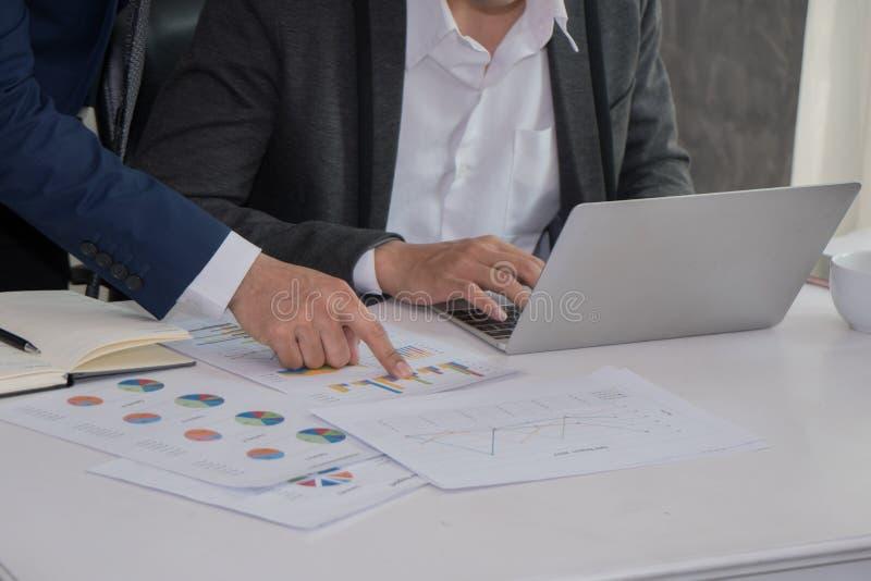 Närbild av den mänskliga handen som pekar på rapporten i papper medan colleag royaltyfri foto