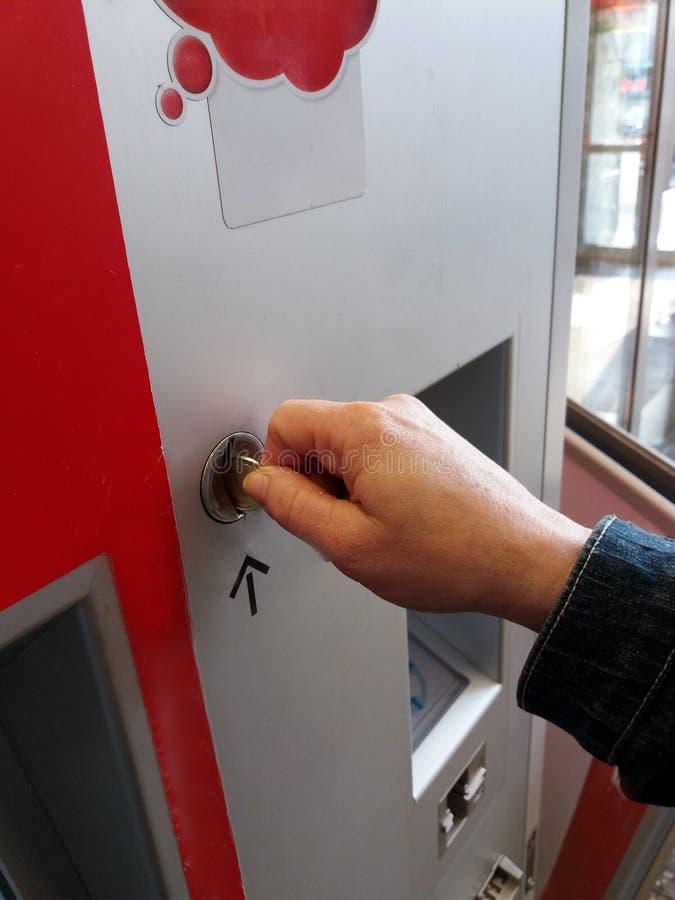 Närbild av den mänskliga handen som sätter in myntet i varuautomat royaltyfria foton