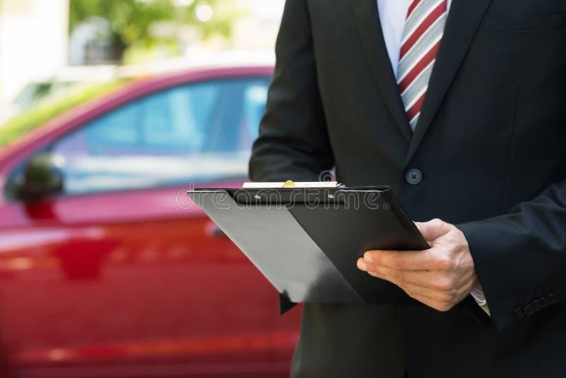 Närbild av den manliga hållande skrivplattan nära bilen royaltyfri bild