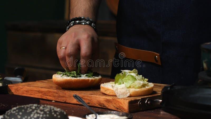 Närbild av den manliga kocken i det blåa förklädet som tar bort de överskott gräsplanerna från en hamburgarebulle Materiell?ngd i royaltyfria bilder