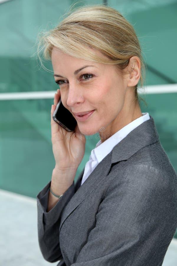 Närbild av den medelåldersa affärskvinnan som talar på smartphonen royaltyfria foton