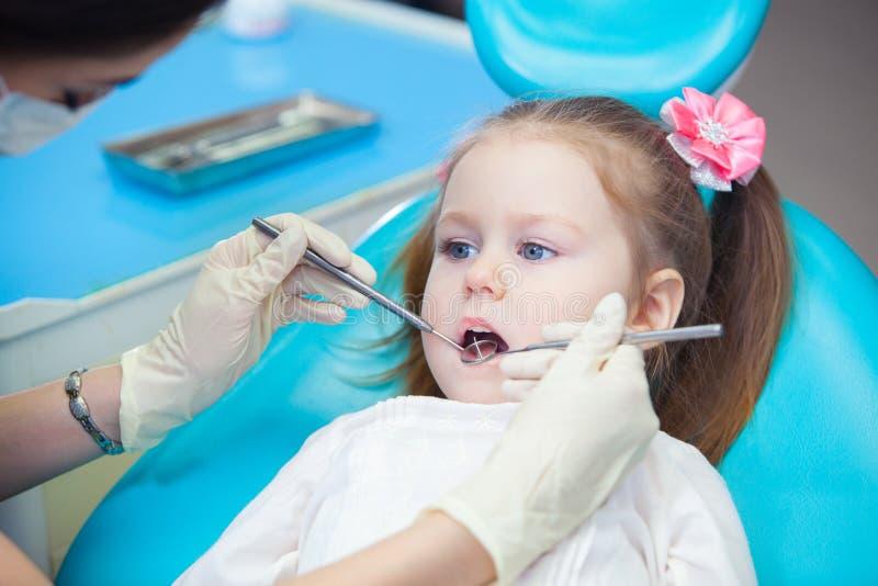 Närbild av den nätta lilla flickan som öppnar hans munsned boll under kontroll av det muntliga hålet på tandläkaren arkivfoto