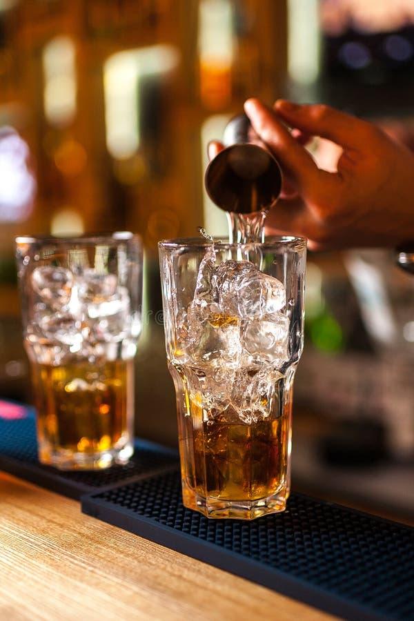 Närbild av den sakkunniga bartenderdanandecoctailen i stång, färgstänk av whisky och rom arkivbilder