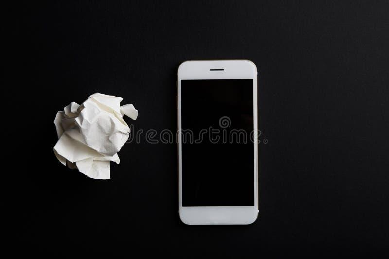 Närbild av den skrynkliga pappers- mobiltelefonen för bollslutpf på svart bakgrund arkivfoton