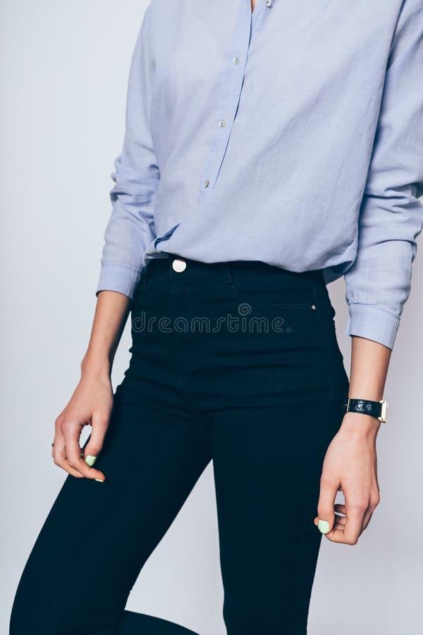 Närbild av den spensliga unga kvinnliga modellen som bär svart mager jeans arkivbilder