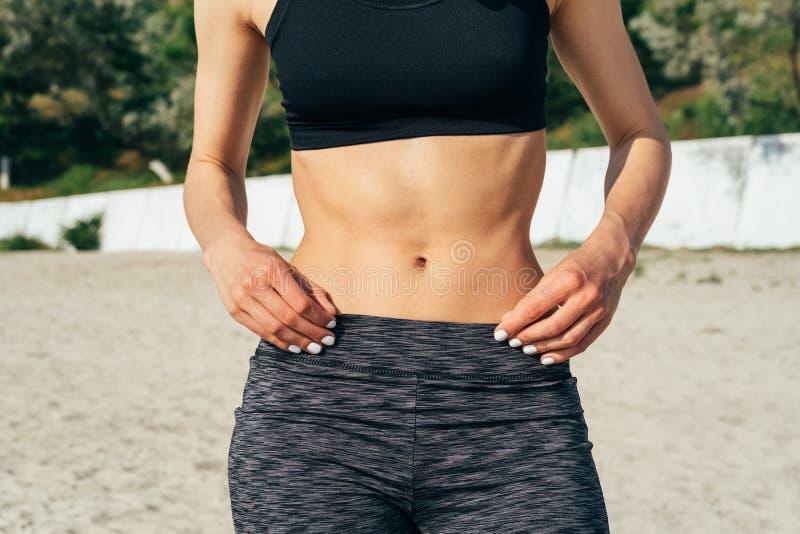 Närbild av den sportiga flickan med en plan buk på stranden royaltyfri bild