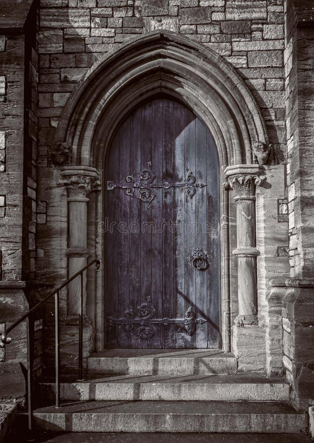 Närbild av den traditionella gotiska medeltida träingångsdörröppningen med den forntida tegelstenbågen, mystisk portal arkivfoto