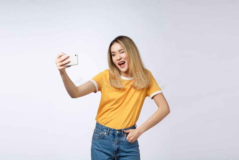 Närbild av den unga asiatiska härliga kvinnan som tar selfie Isolerad vitbakgrund Skönhet och sund kvinna royaltyfri fotografi