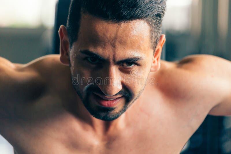 Närbild av den unga Caucasian muskulösa modellen för rasande och ilsken manlig kondition som lyfter tunga hantlar royaltyfri bild