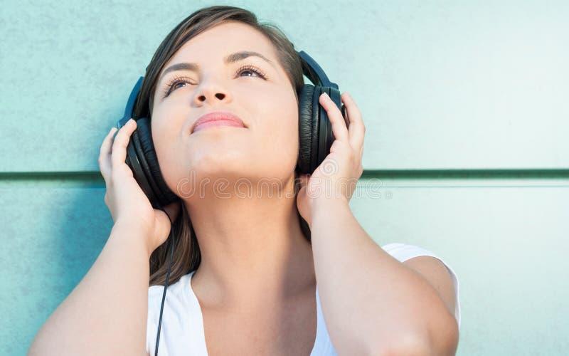 Närbild av den unga härliga flickan som tycker om musik på hörlurar royaltyfria bilder