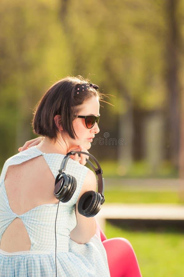 Närbild av den unga hipsterkvinnan med hörlurar med mikrofon i parkera royaltyfria foton