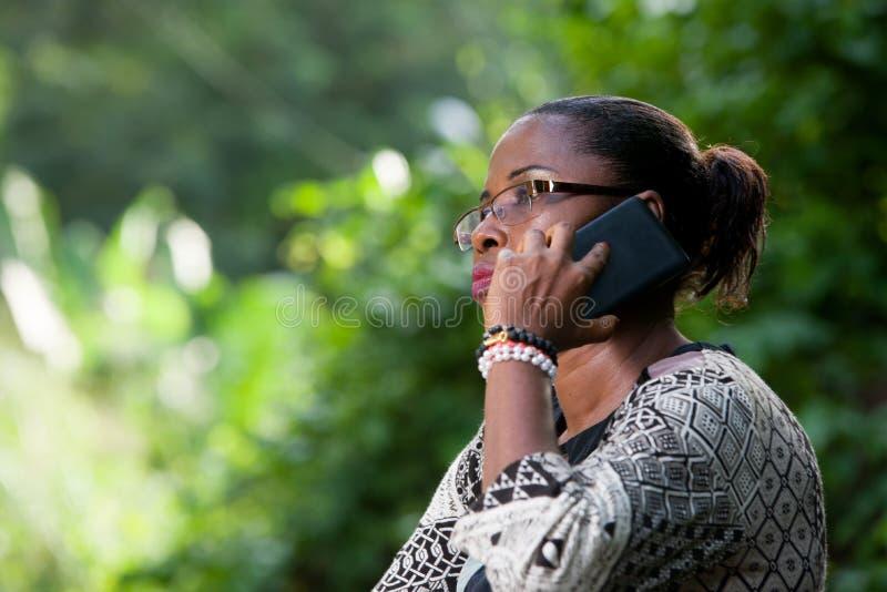 Närbild av den unga kvinnan med mobiltelefonen fotografering för bildbyråer