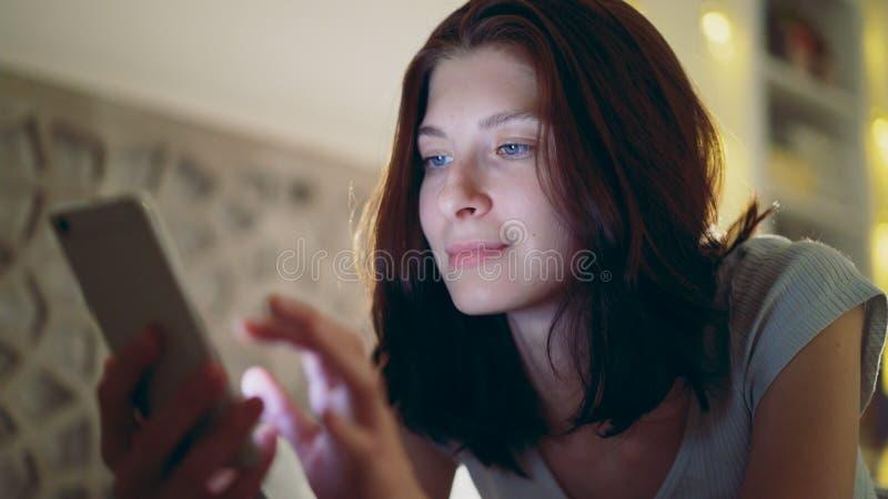 Närbild av den unga le kvinnan som använder smartphonen som hemma ligger i säng på natten royaltyfri bild