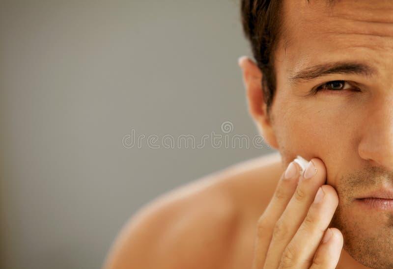 Närbild av den unga mannen som applicerar raka kräm arkivfoto