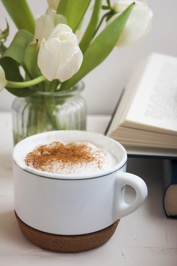 Närbild av den varma koppen kaffe som strilas med kanel arkivbilder