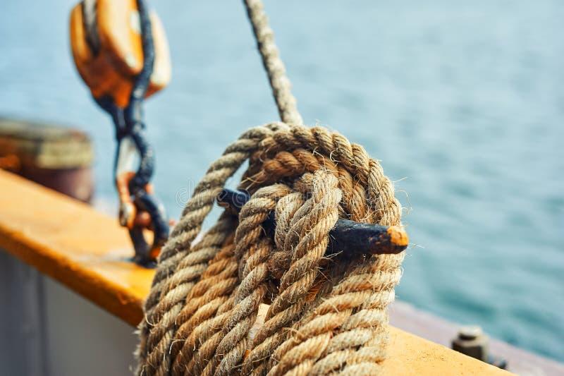 Närbild av det förtöja repet som binds runt om pollaren på skeppet Tillbehöret av seglar royaltyfria foton