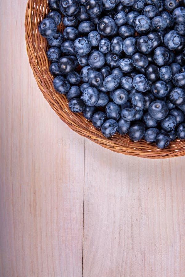 Närbild av det nya och ljusa blåbäret Sunt, moget, rått och ljust mörker - blåa bär på en träbakgrund kopiera avstånd royaltyfri bild