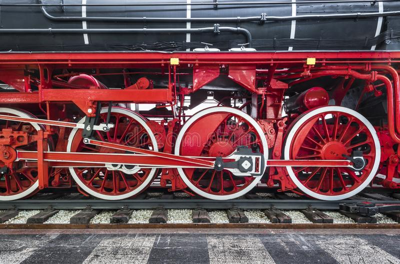 Närbild av det svarta arvångadrevet på järnvägsspår med röda hjul och överföringsmotorn royaltyfri fotografi