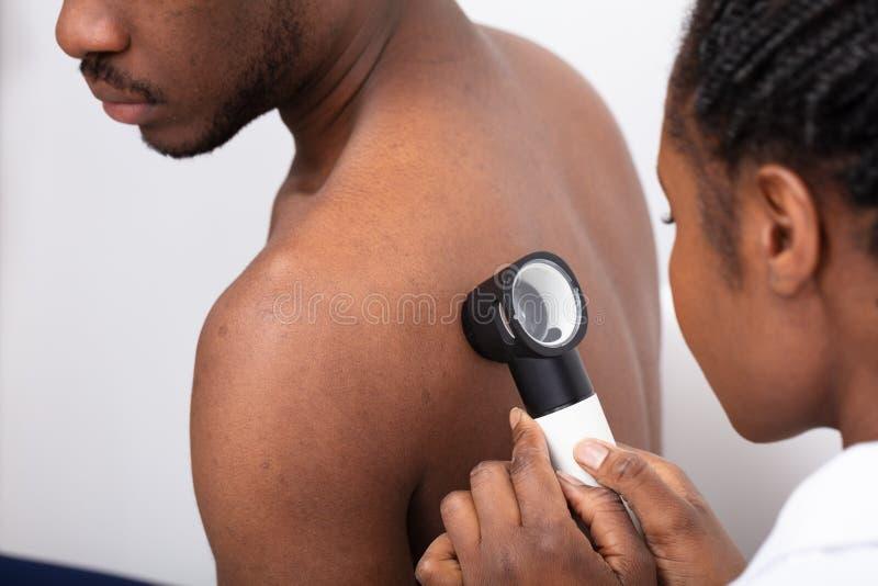 N?rbild av a-doktor Checking Pigment Skin p? mans baksida royaltyfria foton