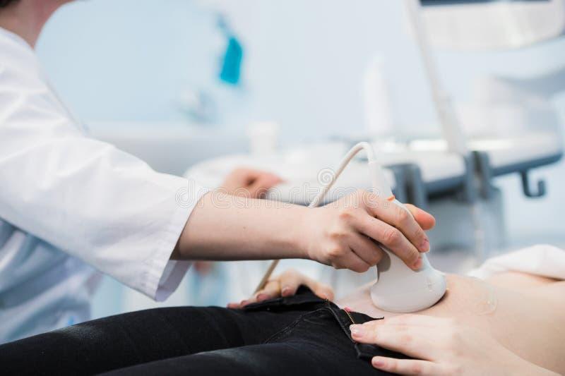 Närbild av doktor Moving Ultrasound Probe på magen för gravid kvinna` s i sjukhus fotografering för bildbyråer