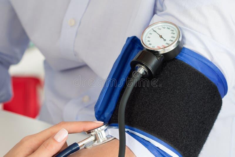 Närbild av doktors händer som mäter blodtryck till hennes man royaltyfria foton