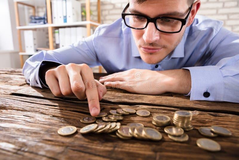 Närbild av en affärsman Counting Coins royaltyfri bild