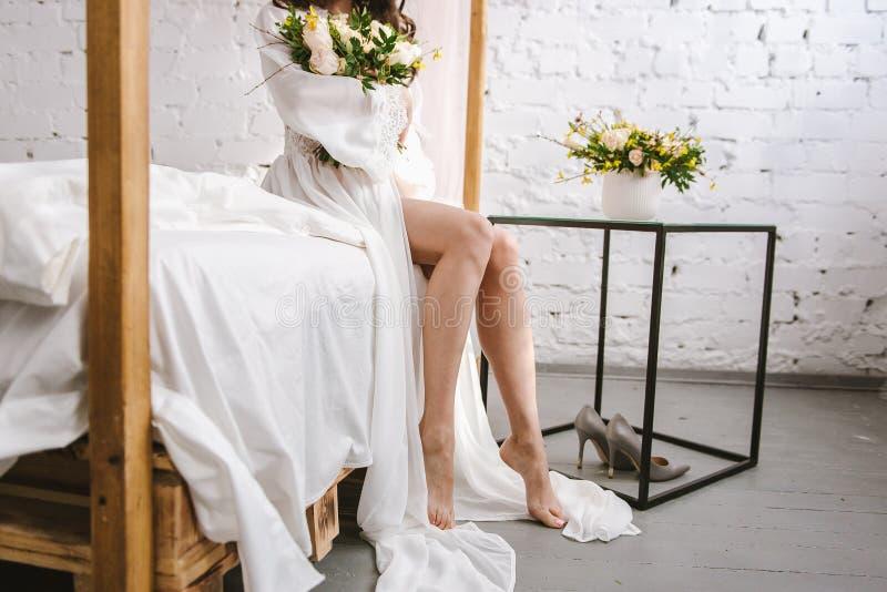 Närbild av en brudpeignoir Morgon av bruden Avgifter för brud` s underkläder Säng royaltyfria bilder