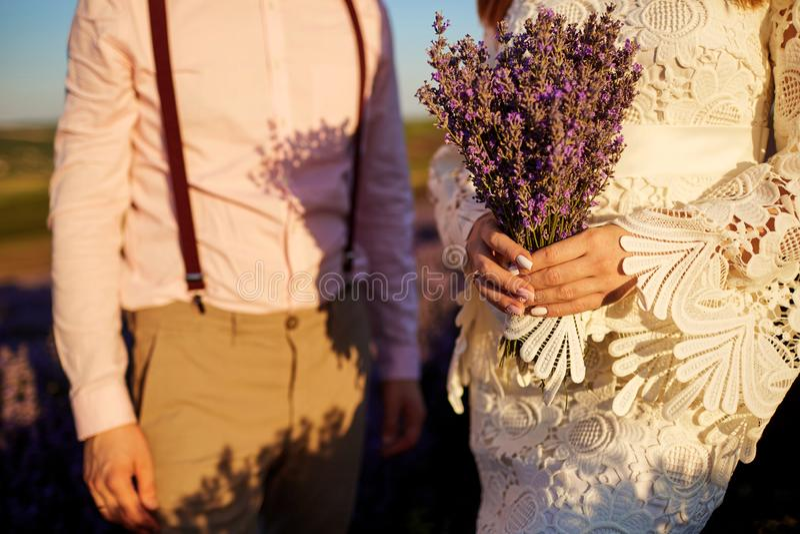 Närbild av en bukett av lavendel i händerna av bruden och brudgummen royaltyfri fotografi