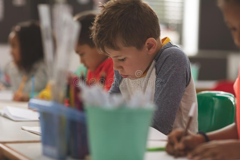 Närbild av en Caucasian skolapojke som skriver en diktamen på en anteckningsbok i ett klassrum arkivfoton