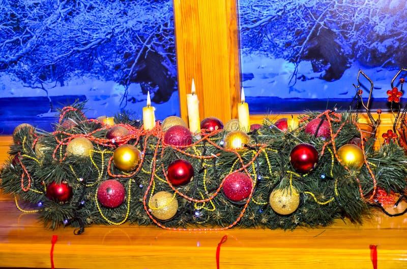 Närbild av en dekorerad girland från filialerna av ett träd för nytt år med julpynt och tända stearinljus royaltyfri fotografi