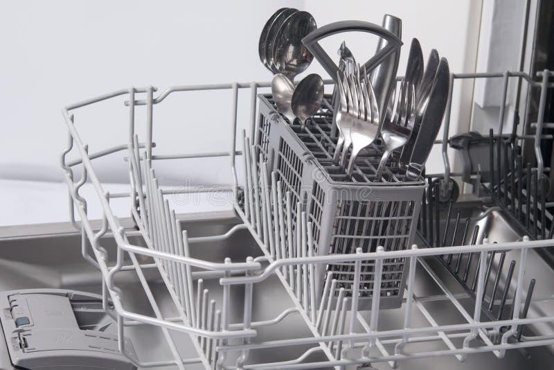 Närbild av en diskarebehållare, med bestick, gafflar, skedar, knivar, efter arbete royaltyfri foto