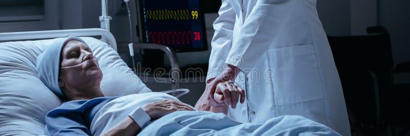 Närbild av en doktor som kontrollerar puls av hans dö av cancerpatie arkivfoton
