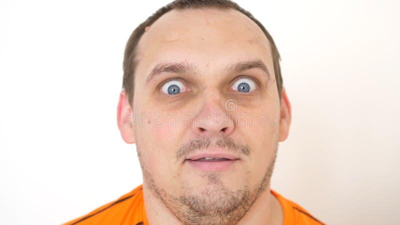 Närbild av en förvånad emotionell skäggig man med blåa ögon som ser in i kameran på en vit bakgrund arkivbilder